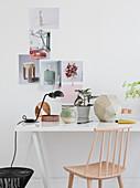 Sprossenstuhl am Schreibtisch vor weißer Wand mit Collage
