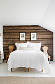 Rustic wooden wall behind bed in country-house bedroom