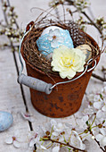 Primulas and Easter egg with lace ribbon in Easter nest in little bucket