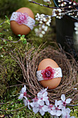 Egg with lace ribbon and cherry plum blossom in Easter nest