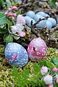 Artistically painted wooden Easter eggs next to apple blossom