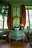 Zwischen Fenstern und Vorhängen platzierte antike Kommode in grünem französischen Salon