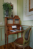 Cane chair at antique writing desk with glass doors