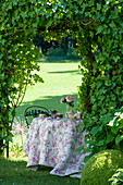 Romantisch gedeckter Kaffeetisch im sommerlichen Schloßgarten