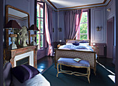 Antique furniture and fireplace in purple bedroom