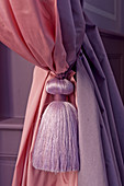 Pink and purple curtains with tasselled tie-back