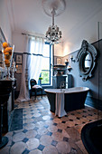 Free-standing bathtub, grand mirror and chandelier in antique-style bathroom
