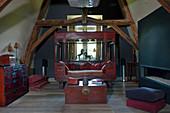 Antikes Holzsofa mit Holzkiste als Couchtisch in Dachraum mit Holzbalkendecke