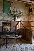 Chandelier and candelabras on table in old stable