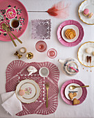 Table set for tea decorated with vintage-style crocheted doilies and floral plates in shades of dusky pink