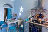 Christmas decorations on cooker and dining table in blue kitchen