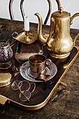 Golden jug, cup and metal candle holder on tray