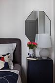 Ranunkeln in Vase mit Gesicht auf dem Nachttisch im Schlafzimmer