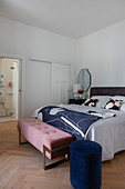 Blue pouffe and bedroom bench in bedroom with ensuite bathroom
