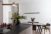 Polsterstühle um modernen Esstisch in der puristischen Wohnküche