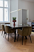 Upholstered chairs around modern dining table in kitchen-dining room with parquet floor