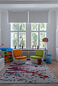 Easy chairs on rug with pattern of multi-coloured splashes in child's bedroom