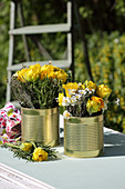 Yellow double tulips in golden tin cans used as vases