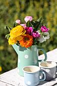 Gerbera daisies, ranunculus and anemones in pastel jug with polka-dot pattern