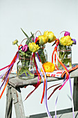 Double tulips in screw-top jars decorated with colourful ribbons