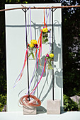 Schraubgläser mit Blumen und bunten Stoffbändern hängen am Ast