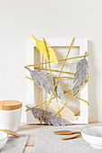 Arrangement of felt feathers and woollen yarn wrapped around picture frame