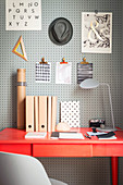 Perforated wooden panel used as note board above desk in study
