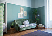 Vintage velvet sofa against green wall in corner of period apartment