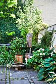 Terrassen-Dekoration mit Kunstobjekt, Kübelpflanzen und Wasserschale