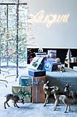 Verpackte Weihnachtsgeschenke dekoriert mit Rehfiguren und Kugeln