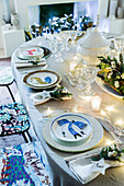 Table festively set with flower arrangement, fairy lights and individual underplates