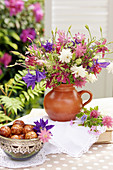 Bouquet of mixed aquilegias and bowl of pastries on terrace table
