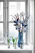 Flowers and branches of pussy willow decorated with paper butterflies on windowsill