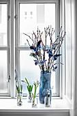 Blumen und Weidenkätzchen mit Papierschmetterlingen am Fenster