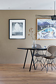 Dining table with designer chairs and photographic art on taupe wall