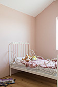 White bed in child's bedroom with pink walls