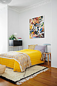 Yellow bedspread on double bed below modern painting in bedroom