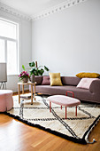 Scatter cushions on sofa, houseplants and side tables on pale rug
