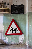 Traffic sign below chalkboard on wall with peeling paint