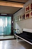 Sitzbank, Fahrrad und Bildergalerie auf Flur mit Betonboden