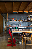 Kitchen and dining area in loft apartment with wooden ceiling and black wall