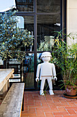 Giant Lego man next to plant on terrace with terracotta floor tiles