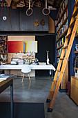 Bücherleiter und großer Tisch in Bibliothek mit dunkler Wand