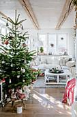 Weihnachtsbaum im sonnigen Wohnzimmer im Landhausstil