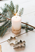 Lit candle, pastry cutters and fir branch