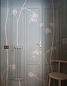Door, wall and radiator painted grey and decorated with stencilled bamboo branches