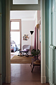 View from hallway into pink interior with vintage rocking chair and standard lamp