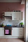 Kitchen with white cupboards, subway tiles and dusky-pink walls in period apartment
