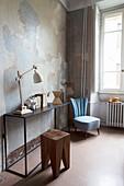 Holzhocker vor schlichtem Metall-Konsolentisch daneben hellblauer Sessel in Altbauwohnung