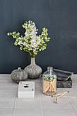 Weißer Flieder in Struktur-Vasen, Kartenspiel und Streichhölzer